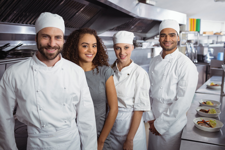 Portrait of restaurant manager with his kitchen staff in the commercial kitchen