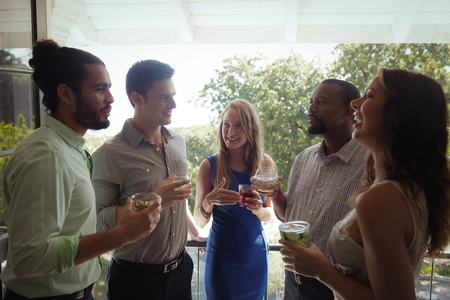 Group of friends interacting with each other while having cocktail drink in restaurant Stock Photo