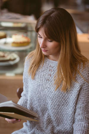 novel: Beautiful woman reading book in the cafe LANG_EVOIMAGES