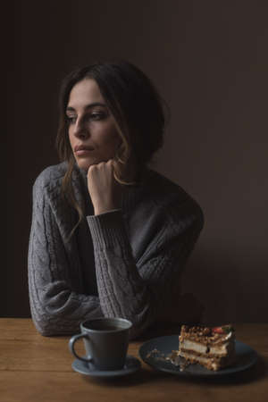 contemplated: Contemplated young woman with hand on chin sitting at table