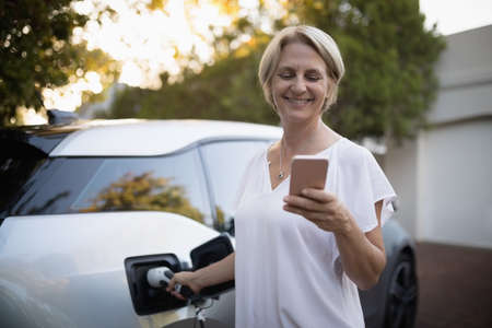 pone: Smiling woman using mobile pone while charging electric car LANG_EVOIMAGES