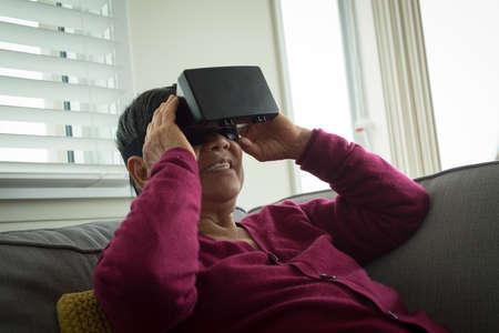 virtual reality simulator: Senior woman using virtual reality simulator while sitting on sofa at home