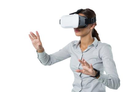 Female executive using virtual reality headset against white background Stok Fotoğraf - 83257668