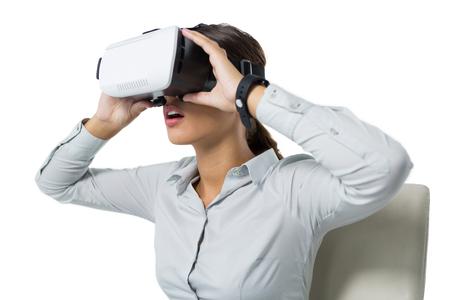 Female executive using virtual reality headset against white background Stok Fotoğraf - 83317557
