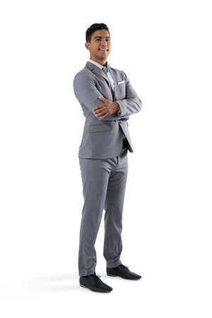 Portrait of businessman standing with arms crossed on white background