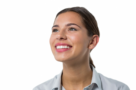 Beautiful female executive smiling against white background