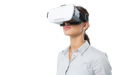 Female executive using virtual reality headset against white background