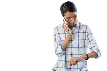 puntualidad: Female executive looking at her wristwatch while talking on the phone against white background