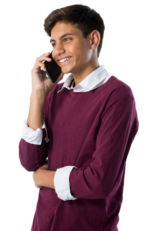 Teenage boy talking on mobile phone against white background