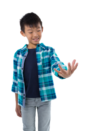 Boy pretending to hold invisible object against white background