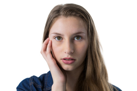 Portrait of confused teenage girl with hand on face