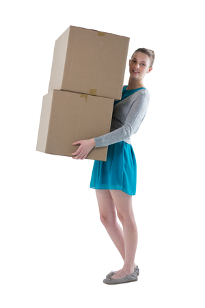 Teenage girl carrying heavy boxes against white background