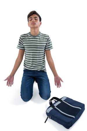 Worried teenage boy praying against white background