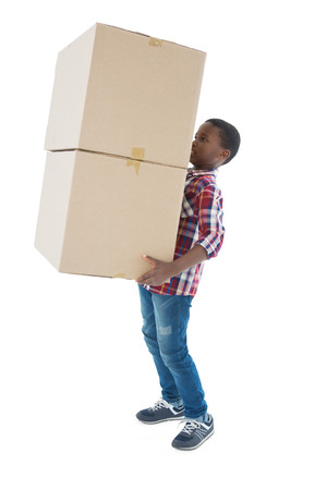 Boy carrying heavy boxes against white background