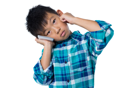 Portrait of boy talking on mobile phone against white background Stock Photo