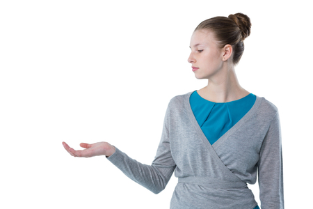 Teenage girl pretending to hold invisible object against white background Stock Photo