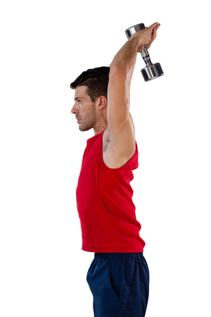 Side view of sportsman exercising with dumbbells against white background
