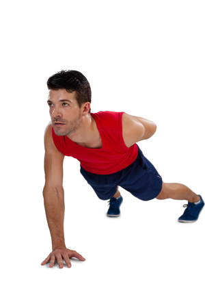 plank position: Full length of sports player exercising against white background