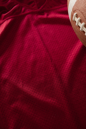 Cropped image of American football on red jersey