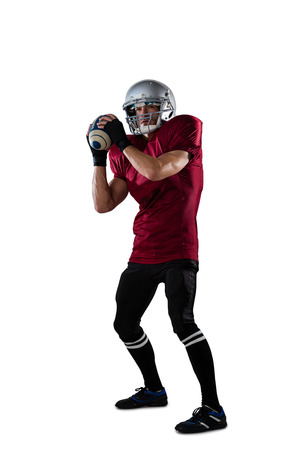 Focused American football player wearing helmet thorwing ball while standing against white background