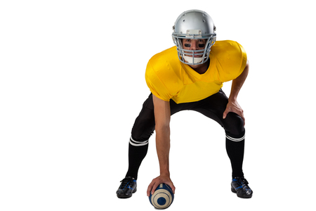 Portrait of American football player wearing helmet bending while holding ball against white background