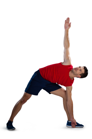 Determined sports player exercising with hand raised while bending against white background Stock Photo