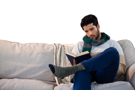 Man sitting on sofa while reading book against white background