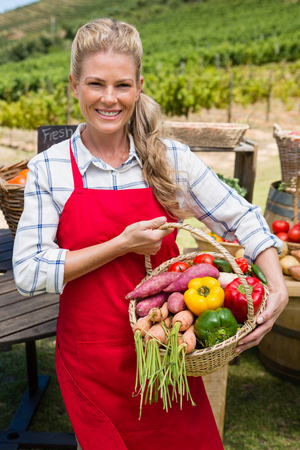 Happy woman holding a basket of fresh vegetables at stall in vineyard