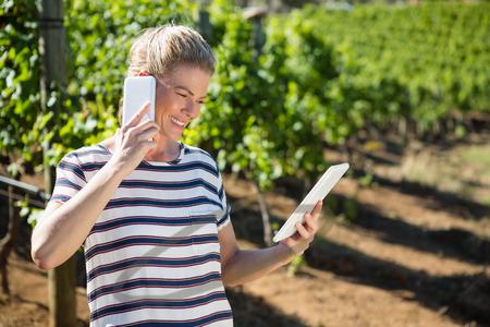 Female vintner using digital tablet while talking on mobile phone in vineyard