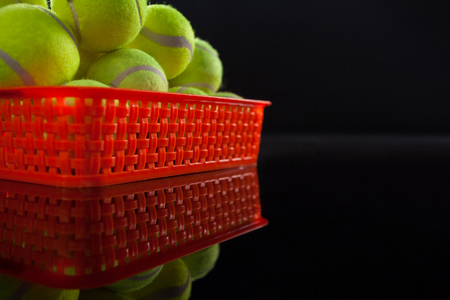 Pile of fluorescent yellow tennis balls in red plastic basket with reflection against black background Stock Photo
