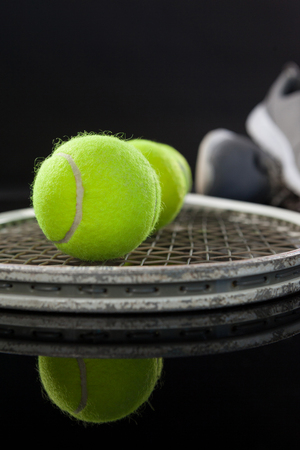 Close up of fluorescent yellow tennis balls on racket by sports shoes with reflection against black background Stock Photo