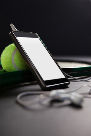 Close up of smartphone and headphones by tennis ball with racket on black background