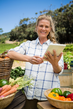 Happy woman using digital tablet at vegetable stall in vineyard