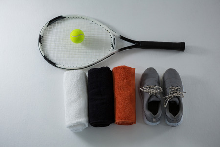 shoe strings: Overhead view of ball on racket by napkins and sports shoe over white background
