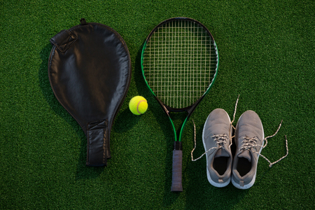 shoe strings: Directly above shot of racket with ball and sports shoes on field Stock Photo