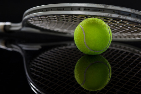 Close up of racket on fluorescent yellow tennis ball with reflection against black background