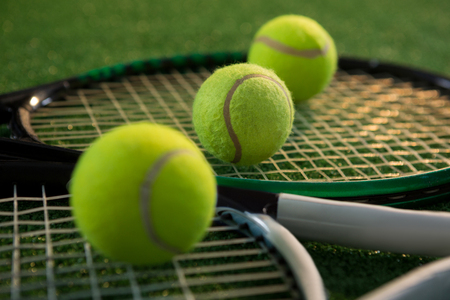 Close up of tennis balls with rackets on field