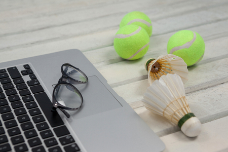 shuttlecock: High angle view of eyeglasses on laptop by shuttlecocks and tennis balls on white wooden table Stock Photo