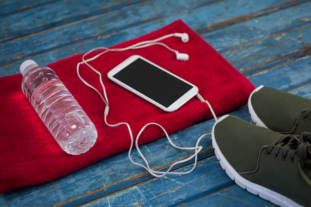 High angle view of water bottle with mobile phone and in-ear headphones on napkin by sports shoes over blue wooden table