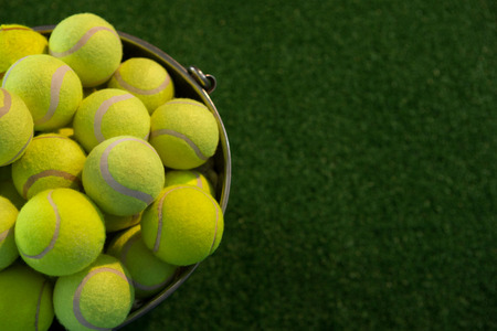 High angle view of fluorescent tennis balls in bucket on field Stockfoto