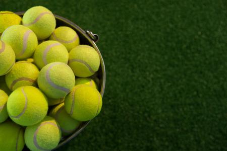 High angle view of fluorescent tennis balls in bucket on field Foto de archivo