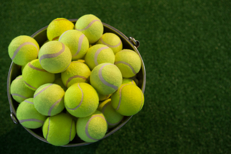 High angle view of tennis balls in bucket on field Stock Photo