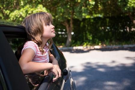 Thoughtful teenage girl looking through car window 免版税图像
