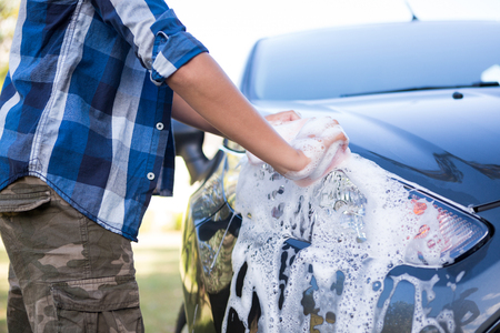 Mid-section of teenage boy washing a car Stock Photo
