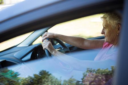 Thoughtful senior woman driving a car
