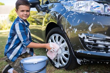 Portrait of teenage boy washing a car on a sunny day