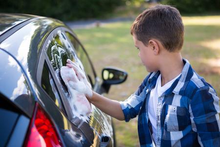Teenage boy washing a car on a sunny day