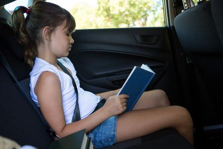 Libro de lectura adolescente atento en el asiento trasero del coche