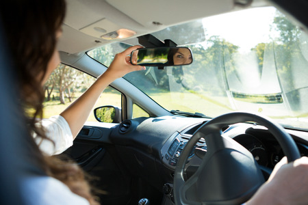 Beautiful woman looking into rear view mirror while driving a car