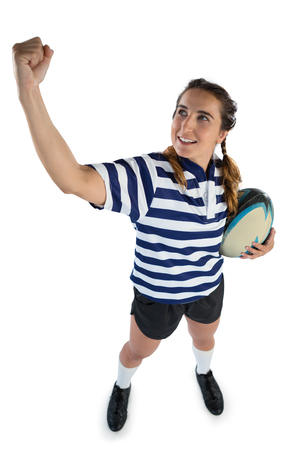 Full length female athlete holding rugby ball while standing with clenching fist against white background Stock Photo
